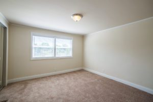 empty bedroom shows window and neutral colors