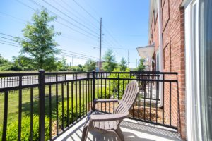ground level patio with iron fencing and lounge chair